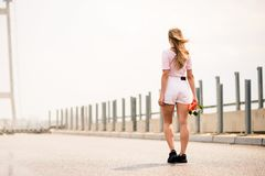Junges schönes blondes Mädchen, das helles Skateboard auf die Brücke reitet Stockbild