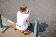 Junges schönes blondes Mädchen, das Smartphone beim Sitzen auf dem Skateboard verwendet Lizenzfreies Stockfoto