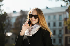 Junges schönes blondes Mädchen in der Sonnenbrille Telefon sprechend Stockfotos
