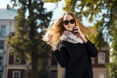 Junges schönes blondes Mädchen in der Sonnenbrille Telefon sprechend Stockbilder