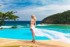 Junges schönes blondes Mädchen in einem weißen Badeanzug mit einem wellenartig bewegenden pl stockbild