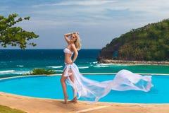 Junges schönes blondes Mädchen in einem weißen Badeanzug mit einem wellenartig bewegenden pl Stockbilder