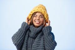 Junges schönes blondes Mädchen im knited lächelnden Blinzeln des Hutes und der Strickjacke, Kamera über blauem Hintergrund betrac Lizenzfreie Stockbilder