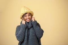 Junges schönes blondes Mädchen im knited lächelnden Blinzeln des Hutes und der Strickjacke, Kamera über gelbem Hintergrund betrac Stockfotos