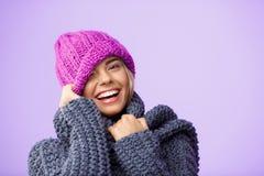 Junges schönes blondes Mädchen im knited lächelnden Blinzeln des Hutes und der Strickjacke, Kamera über violettem Hintergrund bet Lizenzfreie Stockfotos