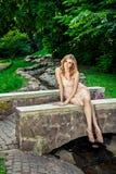 Junges schönes blondes Mädchen im Park Stockfotografie