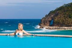 Junges schönes blondes Mädchen ist im Pool Tropisches Meer in Lizenzfreies Stockfoto