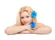 Junges schönes blondes Mädchen mit blauen Blumen Lizenzfreies Stockfoto