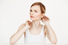 Junges schönes blondes Mädchen mit der sauberen frischen Haut, welche die Kamera bei Tisch sitzt über der weißen Hintergrundkorre Stockbild