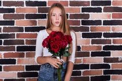 Junges schönes blondes Mädchen mit roten Rosen Lizenzfreies Stockfoto