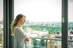Junges schönes blondes Mädchen stehend am Fenster und traurig Lizenzfreies Stockbild
