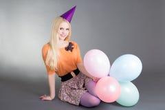 Junges schönes blondes mit den Ballonen, die über Grau sitzen Lizenzfreie Stockbilder