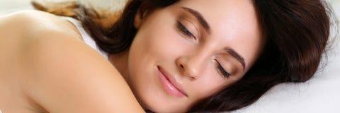 Junges schönes Brunettefrauenporträt, das im Bett liegt stockfoto
