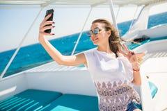 Junges schönes Brunettemädchen, das selfie unter Verwendung des Telefons beim Sitzen auf der Yacht macht Lizenzfreie Stockfotografie