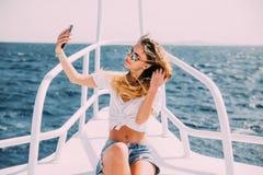 Junges schönes Brunettemädchen, das selfie unter Verwendung des Telefons beim Sitzen auf der Yacht macht Lizenzfreie Stockbilder