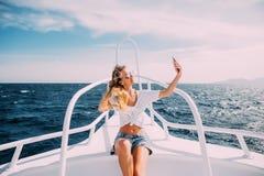 Junges schönes Brunettemädchen, das selfie unter Verwendung des Telefons beim Sitzen auf der Yacht macht Lizenzfreies Stockbild
