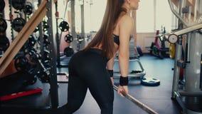 Junges schönes Brunettemädchen mit dem langen Haar in der Turnhalle, die Übungen auf der Hocke mit einer Stange tut 4 K stock video footage