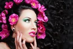 Junges schönes Brunettemädchen mit rosafarbenen Blumen I Stockfoto