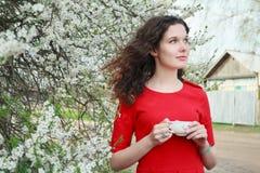 Junges schönes Brunettemädchen mit Teeschale im Arm, der im Frühjahr blühenden Garten steht Stockbild