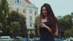 Junges schönes Brunettemädchen steht draußen, schaut herum, beim Warten auf jemand sie ihr Telefon benutzt Positive Stimmung stock video footage