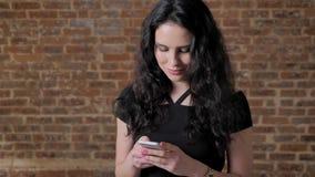 Junges schönes Brunettemädchen surs Internet auf ihrem Smartphone, lächelnd, Kommunikationskonzept, Ziegelstein backgroung stock video footage