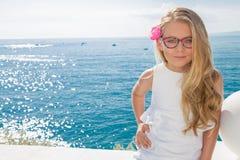 Junges schönes gelocktes blondes Haar des Mädchenmodells lang, das in den rosa Gläsern und in einem schicken Kleid am Pool mit Ge Lizenzfreies Stockbild