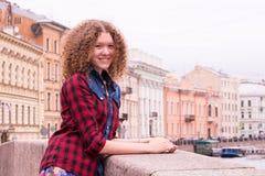 Junges schönes gelocktes jugendlich Mädchen lächelt kokett bei der Stellung auf dem Moika-Fluss in St Petersburg, Russland stockbilder