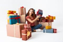 Junges schönes gelocktes Mädchen, das auf Boden unter dem Geschenkboxschätzen sitzt, was nach innen ist Stockbilder