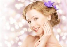 Junges schönes gesundes Mädchen des Schönheitsgesichtes mit den purpurroten und lila Blumen Stockbilder