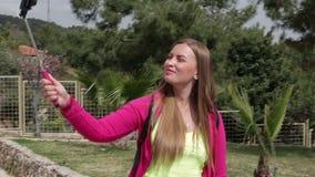 Junges schönes glückliches Mädchen, das ein Foto auf Smartphone im Sommerpark im sonnigen Wetter tut stock video footage