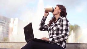 Junges schönes glückliches stillstehendes Mädchen beim Sitzen durch den Brunnen in der Stadt mit Laptop stock video