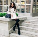 Junges schönes hübsches Mädchen, das entlang der Straße mit schwarzer Handtasche geht und aufwirft lizenzfreie stockbilder