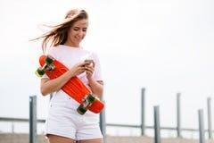 Junges schönes lächelndes blondes Mädchen, das Smartphone beim Sitzen auf dem Skateboard verwendet Stockfoto
