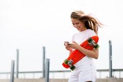 Junges schönes lächelndes blondes Mädchen, das Smartphone beim Sitzen auf dem Skateboard verwendet Lizenzfreies Stockbild