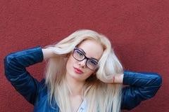 Junges schönes lächelndes blondes Mädchen mit schönem Auftritt und dem langen Haar Lächelndes Mädchen in den Gläsern und in einem Lizenzfreie Stockbilder