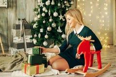 Junges schönes lächelndes Mädchen recht blonde Holding ihre Weihnachtsgeschenke, die nahe Baum sitzen Stockfotografie