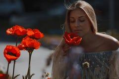 Junges schönes Mädchen auf dem Mohnblumengebiet draußen stockfoto