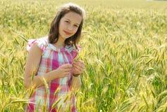 Junges schönes Mädchen auf einem Gebiet des Weizens stockfoto