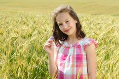 Junges schönes Mädchen auf einem Gebiet des Weizens stockbild
