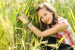 Junges schönes Mädchen auf einem Gebiet des Weizens stockfotos