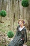 Junges schönes Mädchen auf einem Schwingen im Wald lizenzfreie stockfotos