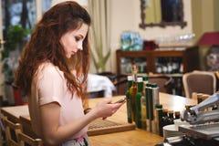Junges schönes Mädchen betrachtet das Telefon zu Hause in der Küche Stockfotos