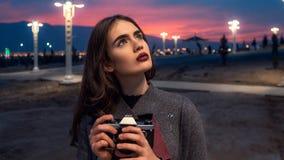 Junges schönes Mädchen in Burgunder-Strümpfen und in den grauen Mantelständen mit Weinlesekamera bei Sonnenuntergang lizenzfreies stockbild