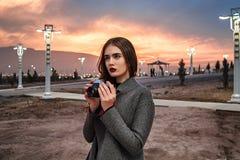 Junges schönes Mädchen in Burgunder-Strümpfen und in den grauen Mantelständen mit Weinlesekamera bei Sonnenuntergang stockfoto