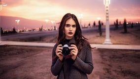 Junges schönes Mädchen in Burgunder-Strümpfen und in den grauen Mantelständen mit Weinlesekamera bei Sonnenuntergang stockbilder