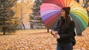 Junges schönes Mädchen, das allein in Herbstpark mit Farbe-ambrella geht 50fps stock video footage