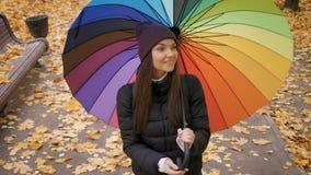 Junges schönes Mädchen, das allein unter Regenschirm im Herbstpark geht stock video