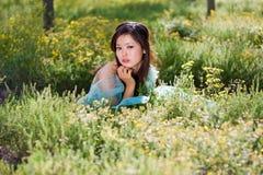 Junges schönes Mädchen, das auf das Blumenfeld legt Lizenzfreie Stockfotografie