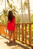 Junges schönes Mädchen, das auf dem Balkon an einem Erholungsort im Hintergrund des Regenwaldes steht Lizenzfreie Stockfotografie