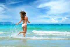 Junges schönes Mädchen, das auf dem Strand läuft Lizenzfreies Stockbild